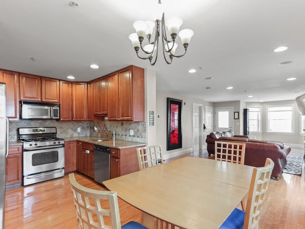 An expansively open kitchen-dining room-living room area with furniture.