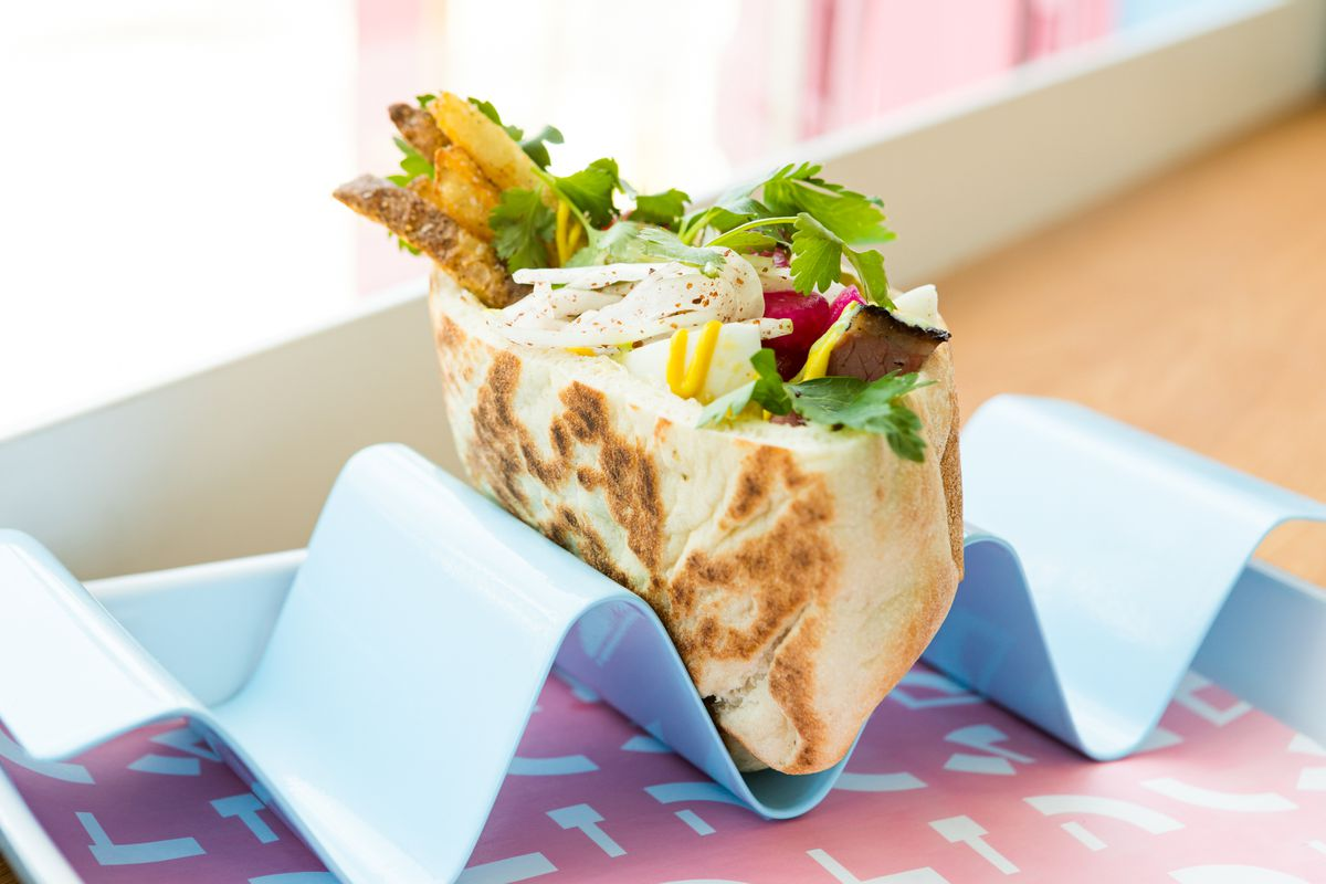 a pita packed with smoked meat, vegetables, and herbs sits in a special holder that keeps it standing upright