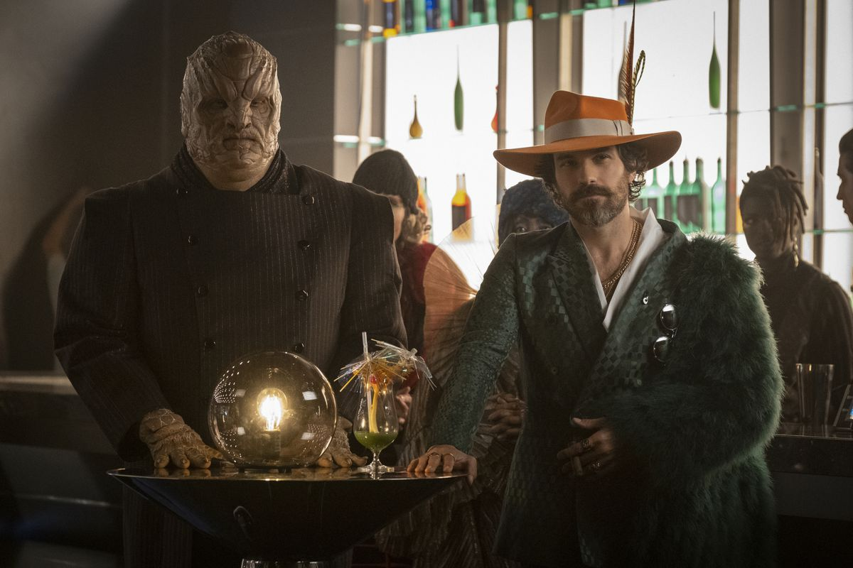 A huge, bald, thick-bodied grey alien stands in a brightly backlit bar next to starship captain Rios, who's in disguise in a ridiculous fuzzy striped green coat and a wide-brimmed, bright red hat with a couple of big jaunty feathers in the brim.
