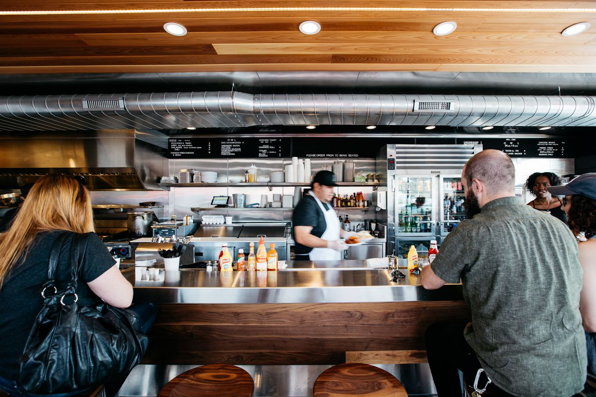 A man and a woman with red hair sit at stools along the metal counter overlooking the kitchen at Owl.