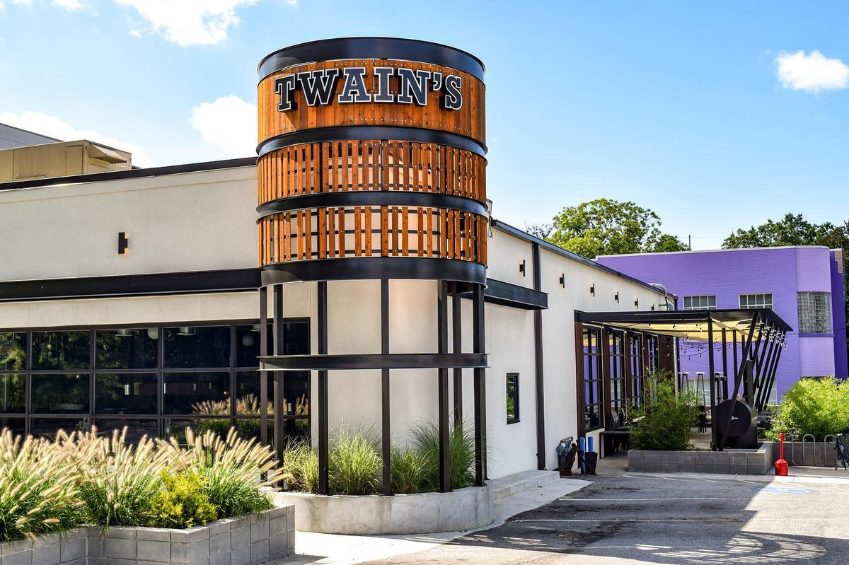 The white and wood exterior of Twains Brewpub and Billiards in Decatur, GA, on sunny, clear blue sky day.