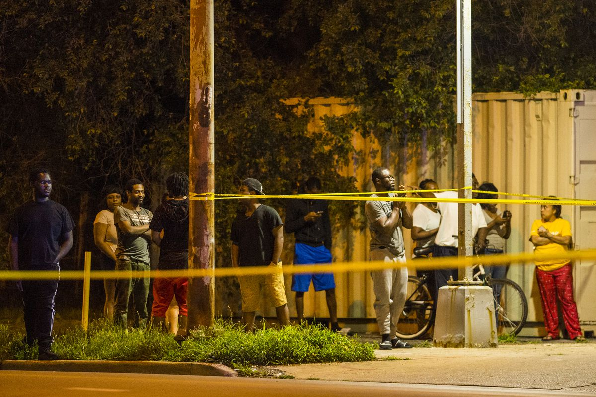 Bystanders watch as police investigate an officer-involved shooting Monday night in the 2300 block of East 79th Street. | Tyler LaRiviere / Sun-Times
