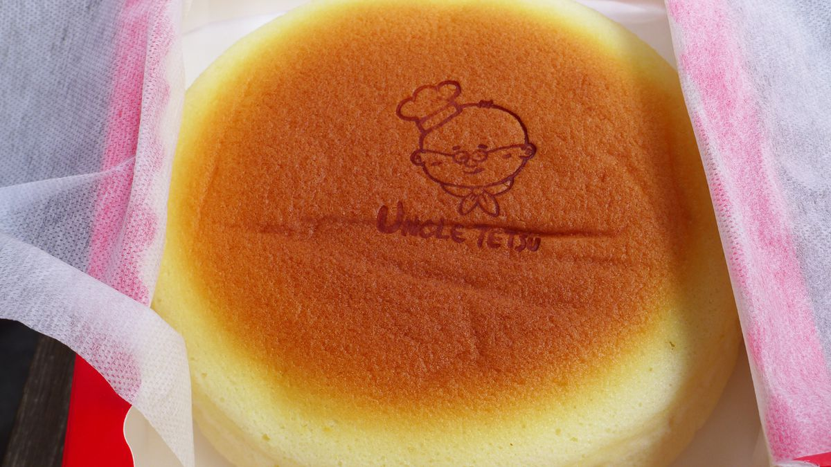 A round brown cheesecake in a red box, with a picture of a chef stamp on top of the cake.