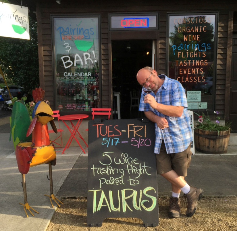 Jeffrey Weissler stands in front of a wine shop, leaning on a chalkboard sign advertising a wine tasting. To the left is a parrot sculpture made out of metal.