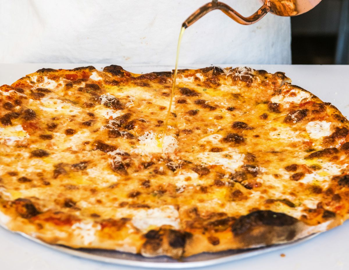 crispy pizza with olive oil being poured on it