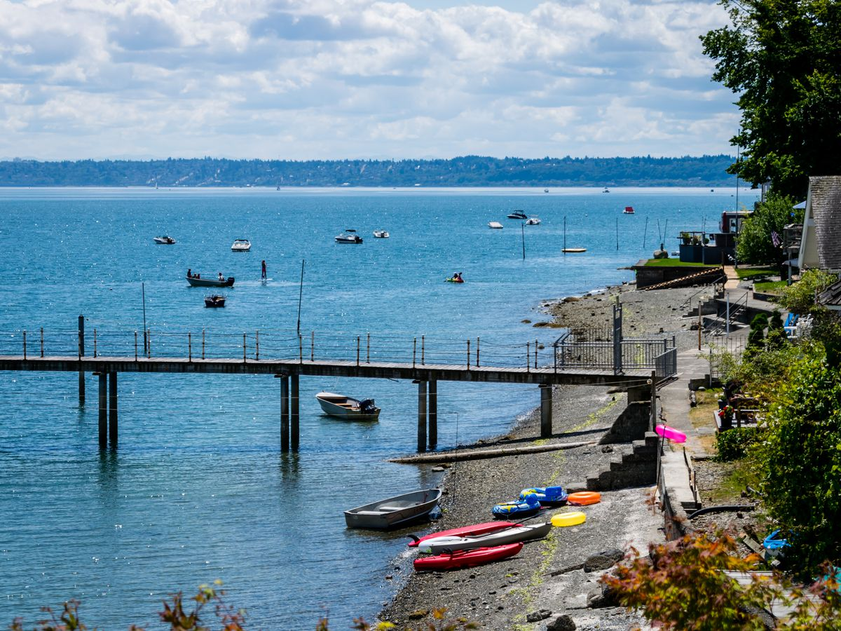 Kayaks sit on a sandy beach. A long, narrow dock juts into the water from a stone bank above the beach. Many small boats are anchored in the water.