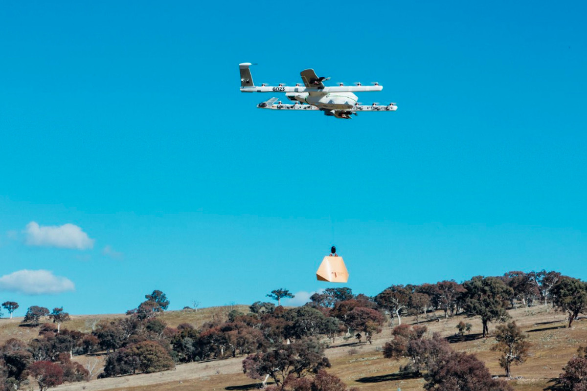 A Project Wing drone flies while carrying a package on a rope below it in order to deliver to a customer in rural Australia.