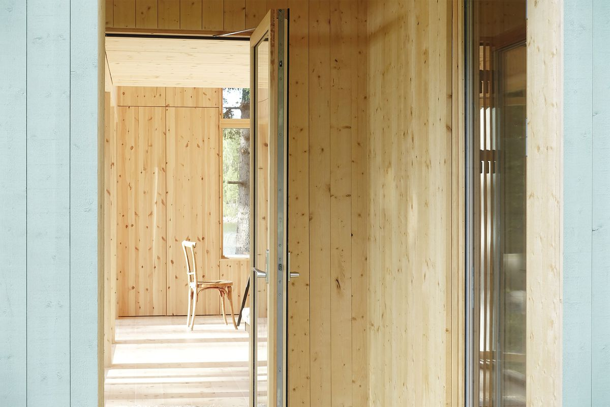 Pale wood interior of house shows a wooden chair in the distance.