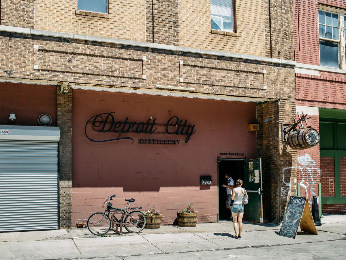 Customers walk through the door of Detroit City Distillery on a warm, sunny day. The exterior is salmon-colored.