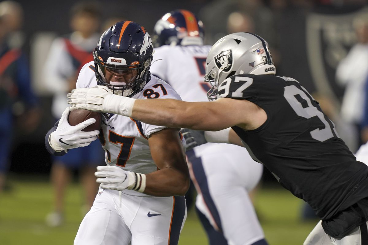 Denver Broncos tight end Noah Fant is defended by Oakland Raiders defensive end Josh Mauro jn the first quarter at Oakland-Alameda County Coliseum.