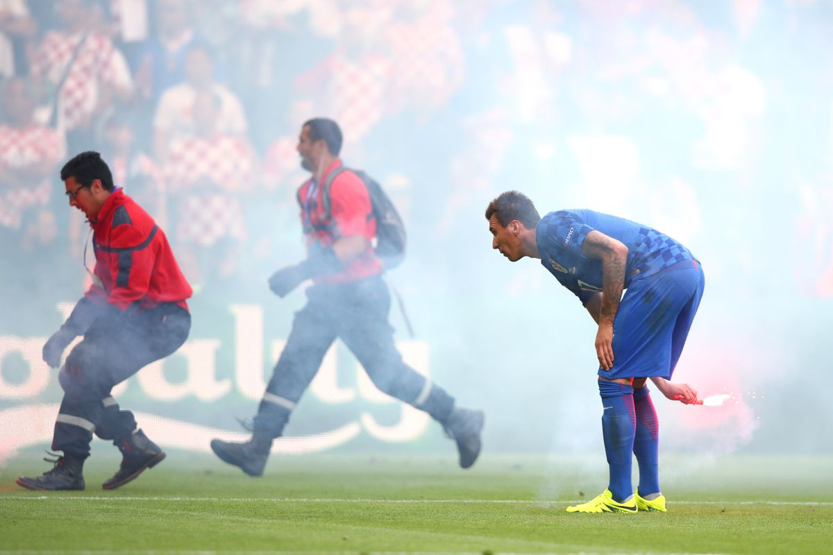 Mario Mandzukic of Croatia helps remove flares from the ptich during the UEFA EURO 2016 Group D match between Czech Republic and Croatia at Stade Geoffroy-Guichard on June 17, 2016 in Saint-Etienne, France.