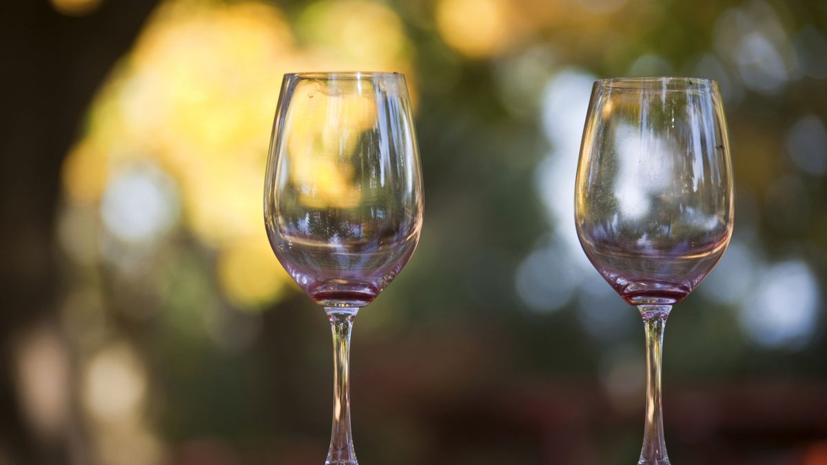 Two empty wine glasses containing traces of red wine sitting on a table outdoors.