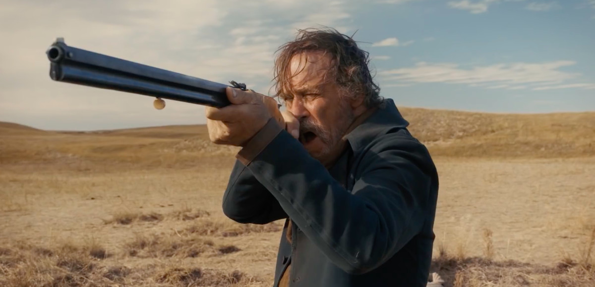 The Ballad of Buster Scruggs - prospector aiming a rifle