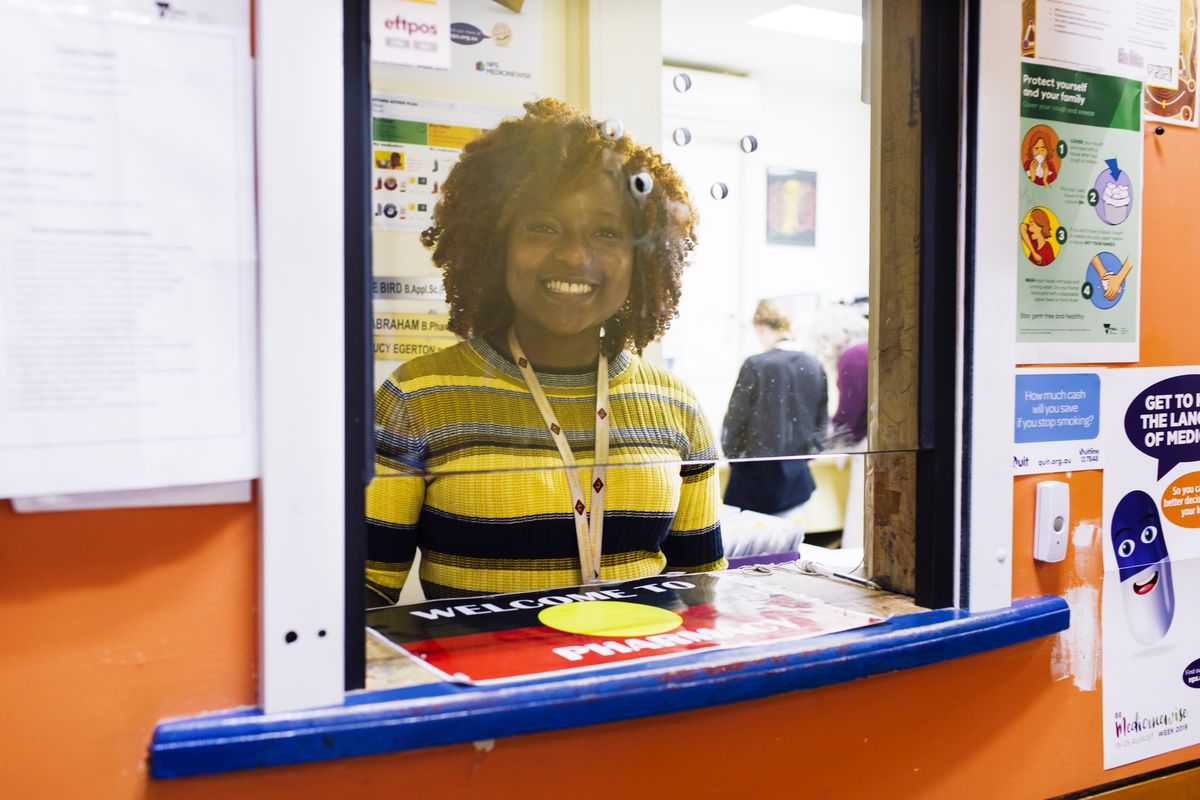 A woman smiles behind a pharmacy counter.