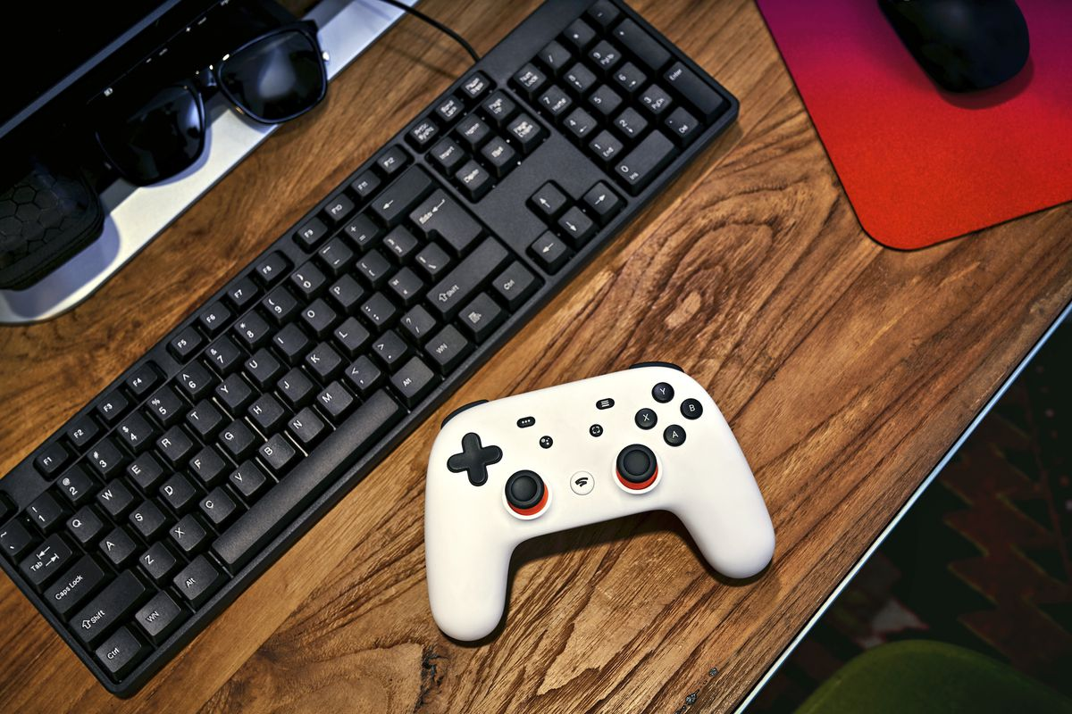 A Google Stadia controller rests on a wood desk next to a black computer keyboard