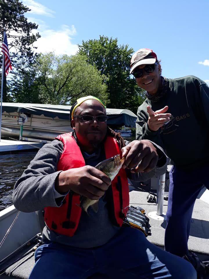 DJ Fyre unhooks a fish on the Wisconsin River with Rob Abouchar in the background. Provided photo