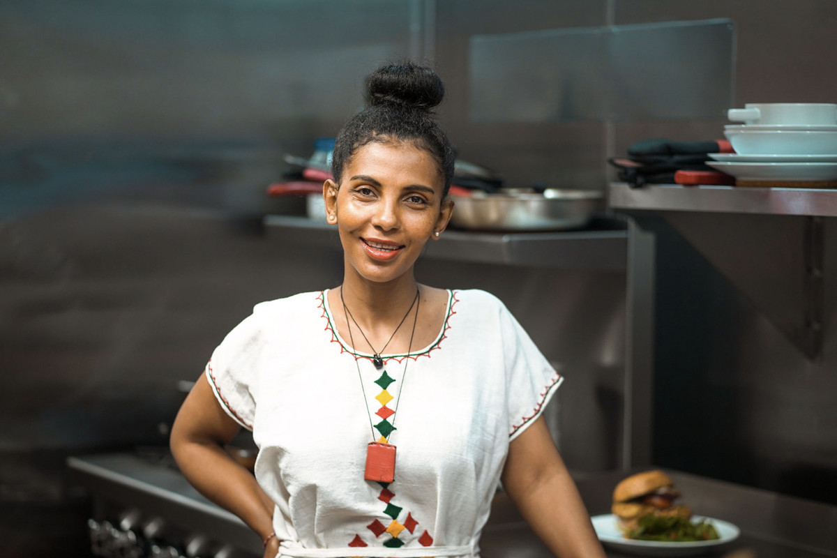 A chef in a white shirt smiles at the camera, hair up, inside of a kitchen.