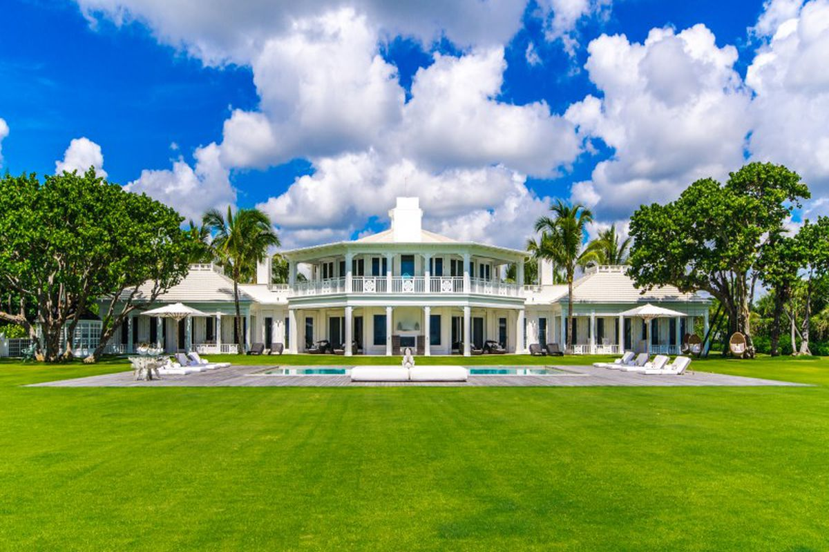 View of a traditional white estate in Jupiter with a large backyard and pool