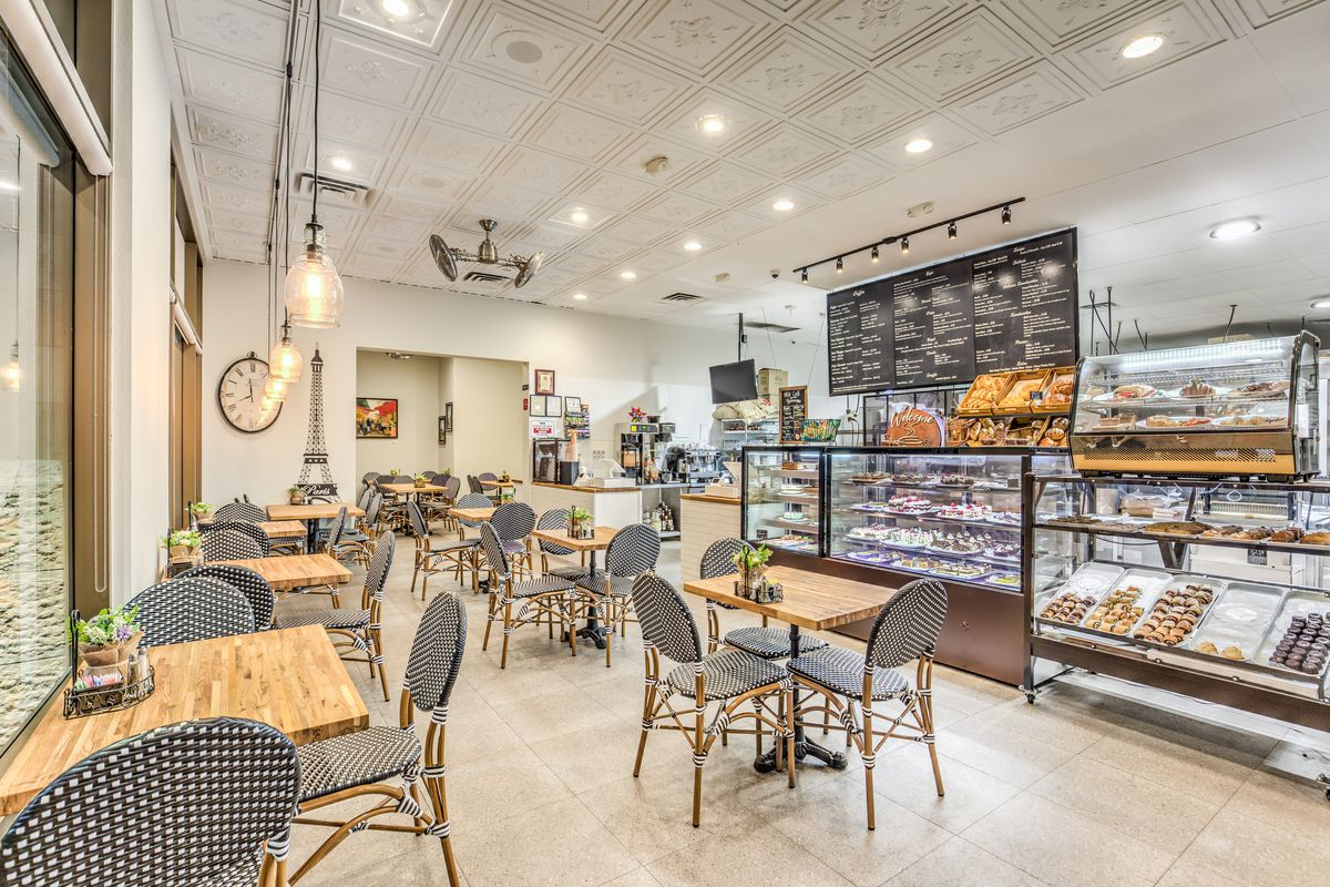 An airy bakery with four-top tables and pastries in a case
