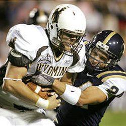 BYU's Spencer White brings down Wyoming's Chris Cox Saturday night in Provo.