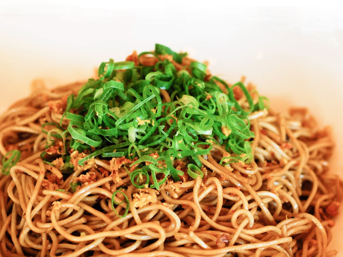 A heaping plate of thin noodles topped with strands of scallion