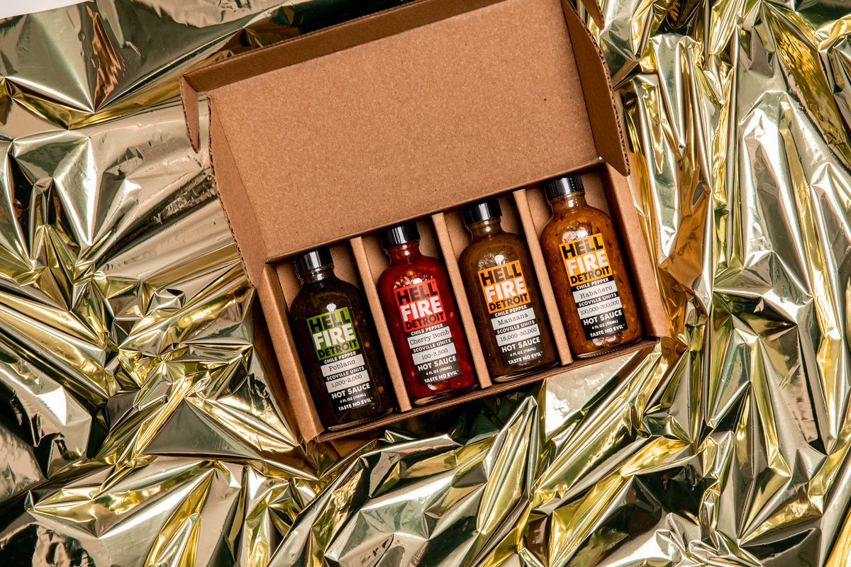 Four different styles of hot sauce in a box.