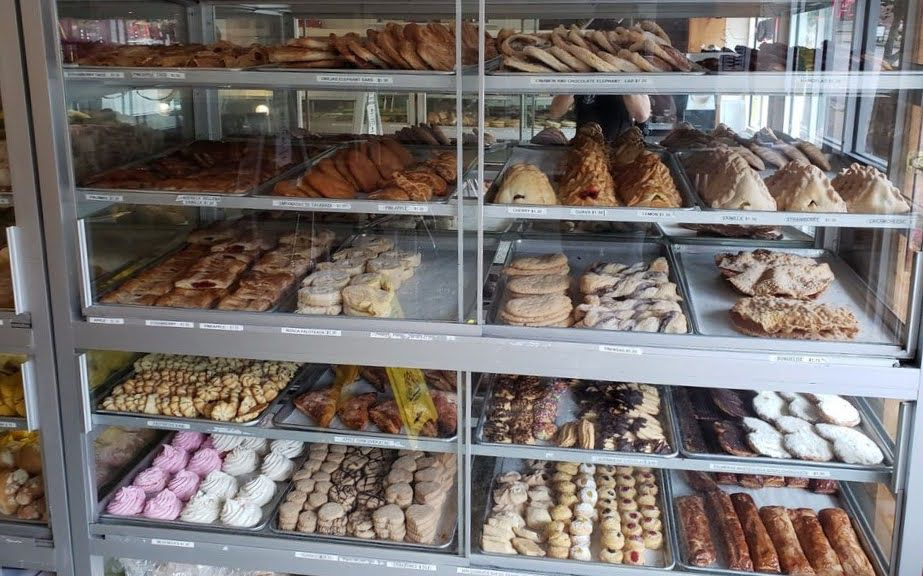 Trays of colorful, decorative cookies and pastries in large sun-lit pastry cases