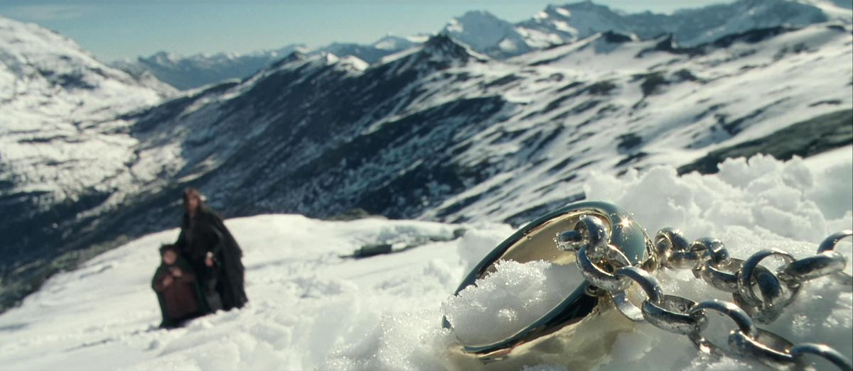 A close up of the One Ring on its bulky silver chain, lying in the snow, from The Fellowship of the Ring.