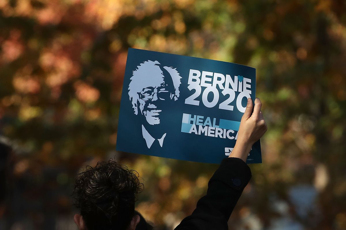 A protester holds up a sign calling for Bernie Sanders to run in 2020.