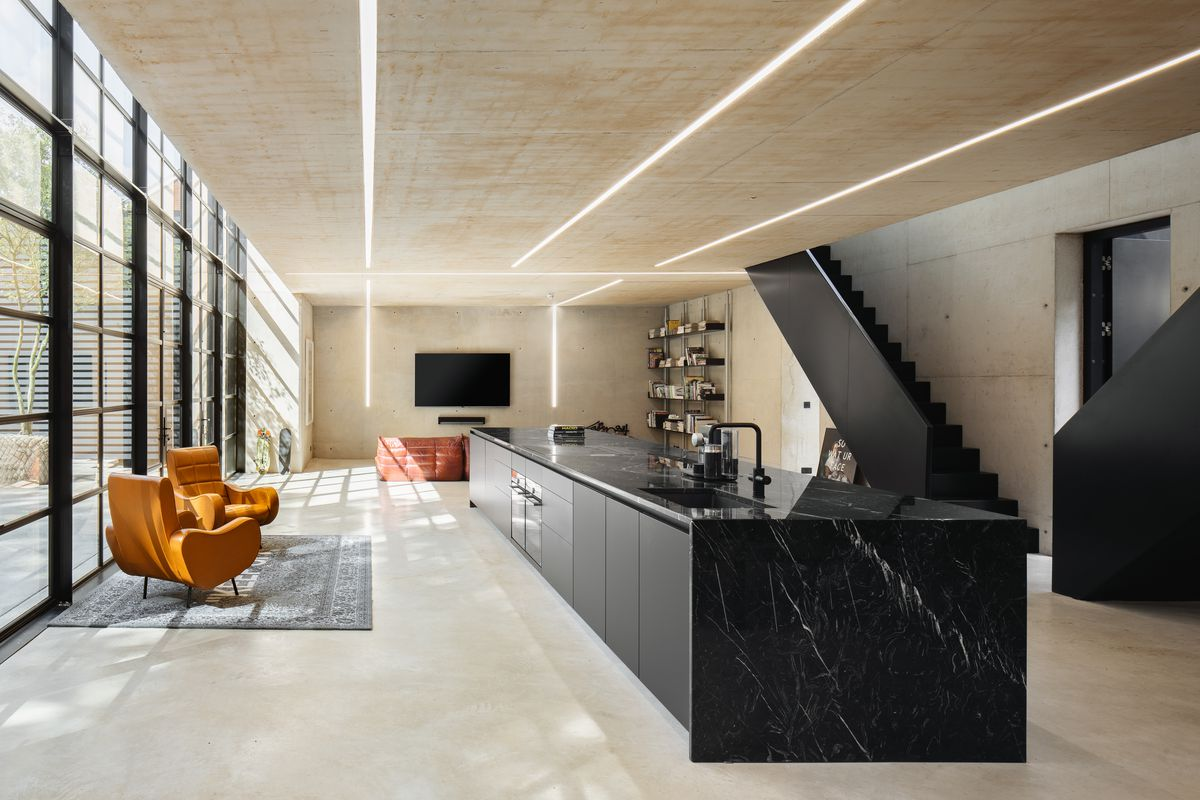 Black marble kitchen island with a living area and TV in the distance.