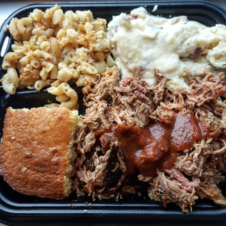 Overhead closeup view of a black plastic takeout container stuffed with mac and cheese, mashed potatoes, pulled pork with barbecue sauce, and cornbread