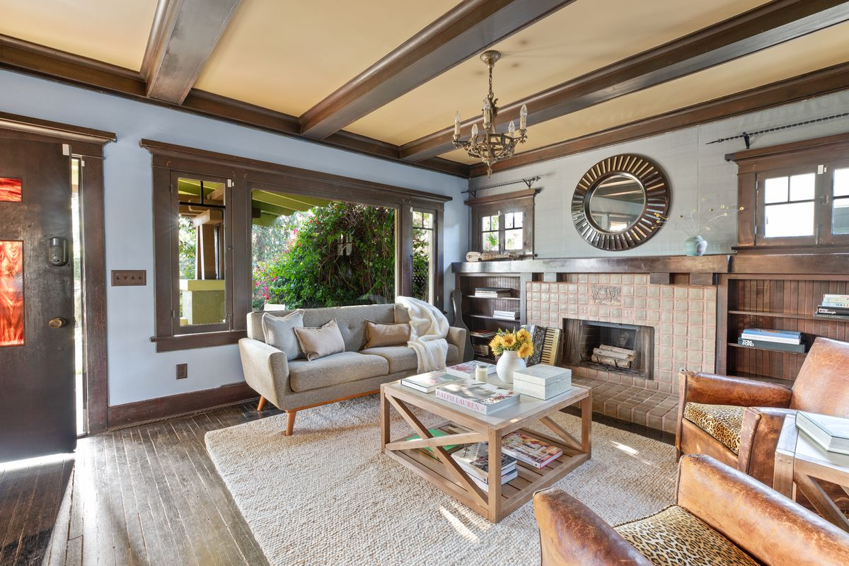 Living room with wood beam ceilings and a tiled fireplace.