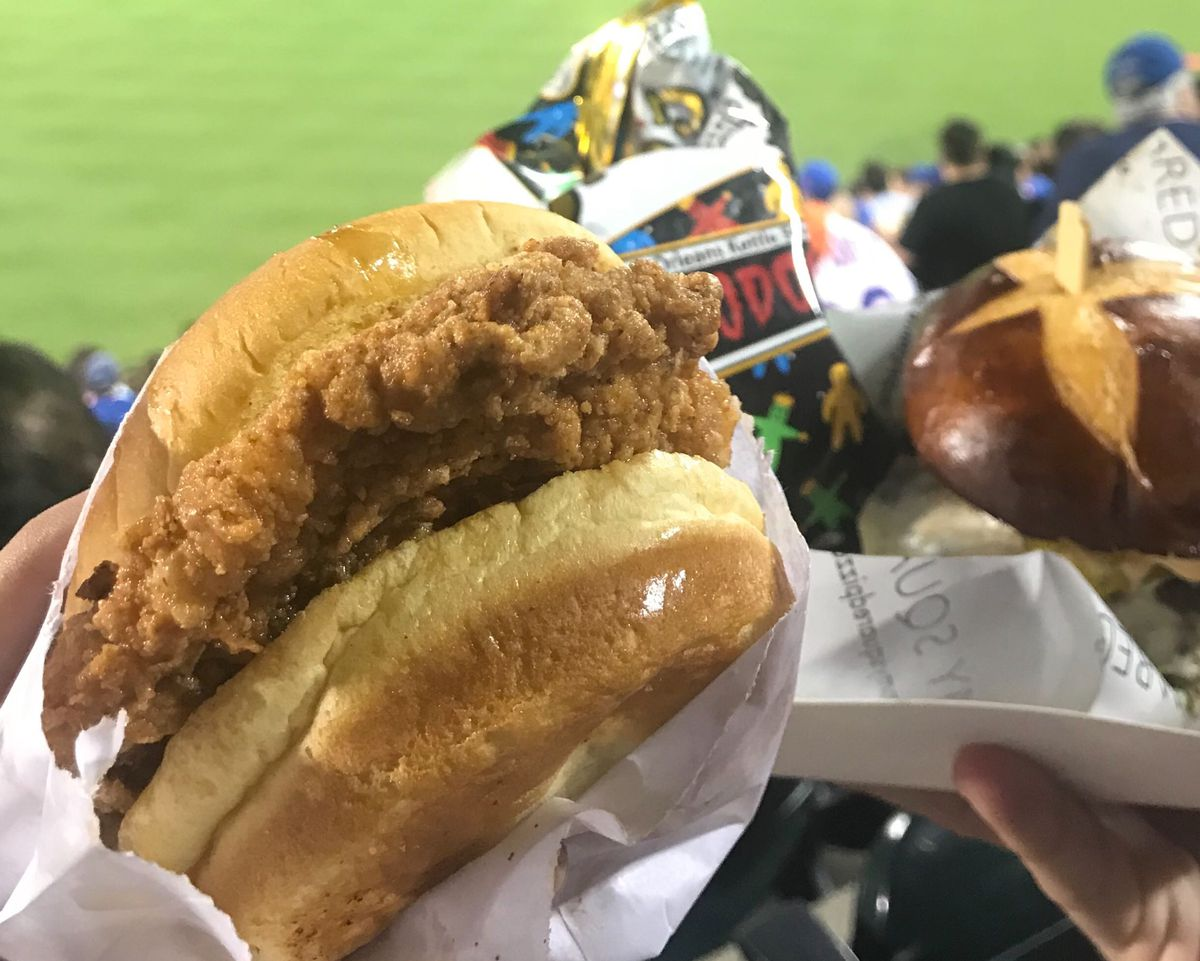 A fried chicken sandwich being held up at a baseball field