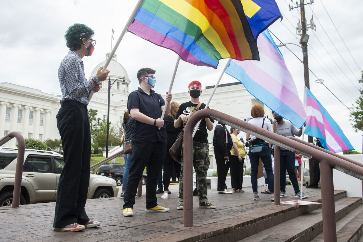 In this Tuesday, March 30, 2021 file photo, demonstrators in support of transgender rights hold flags during a rally outside the Alabama State House in Montgomery, Ala.
