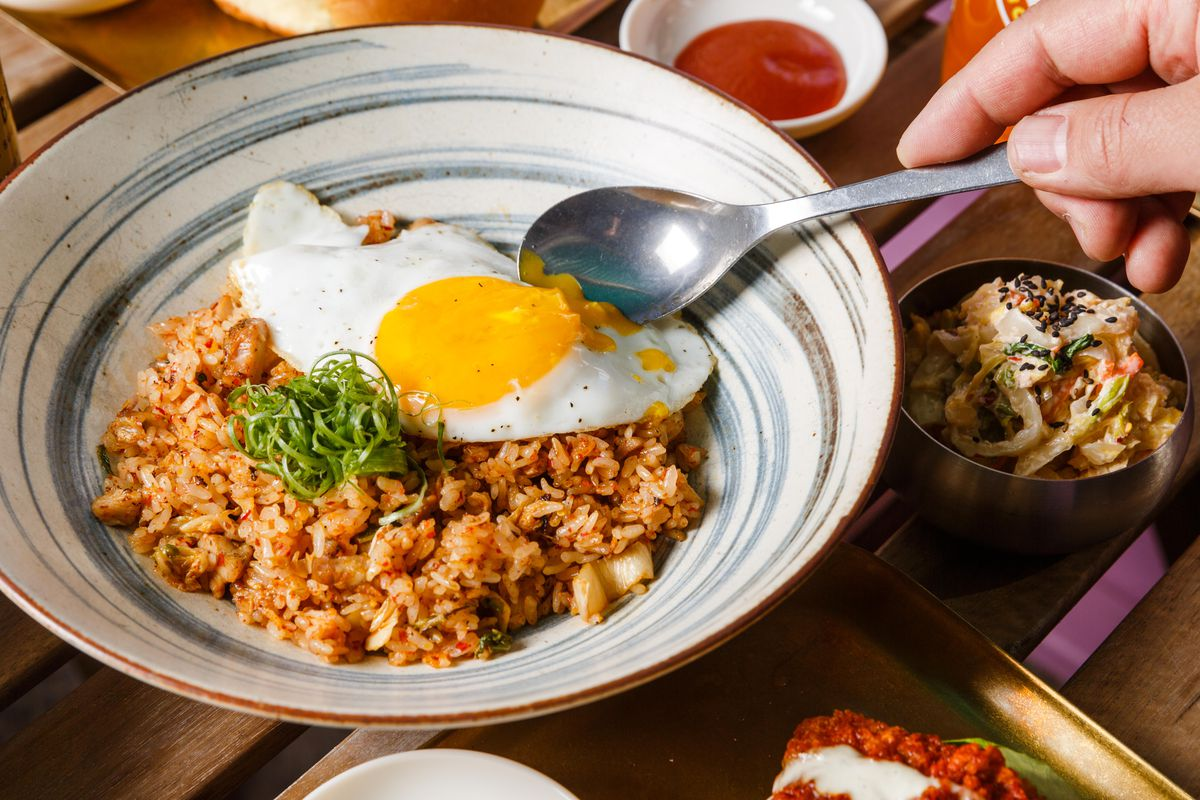 A diner breaks into the yolk atop kimchi fried rice, which sits in a decorative bowl