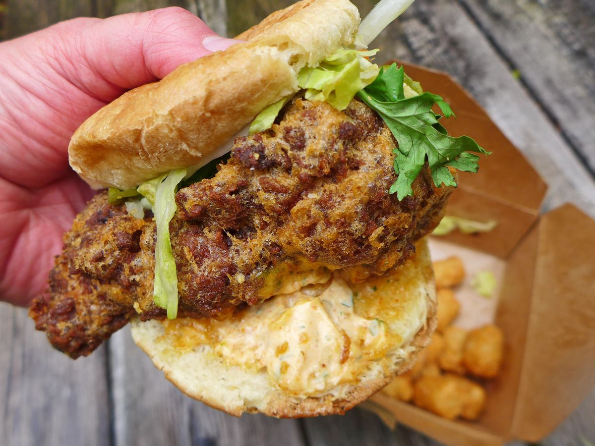 A fried chicken sandwich with a gigantic hunk of chicken held by a hand and with tater tots in a box underneath.
