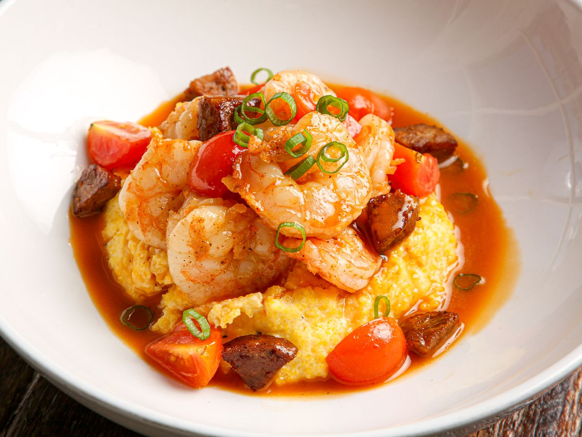 A bowl of shrimp and grits with cherry tomatoes, sausage, and green onion