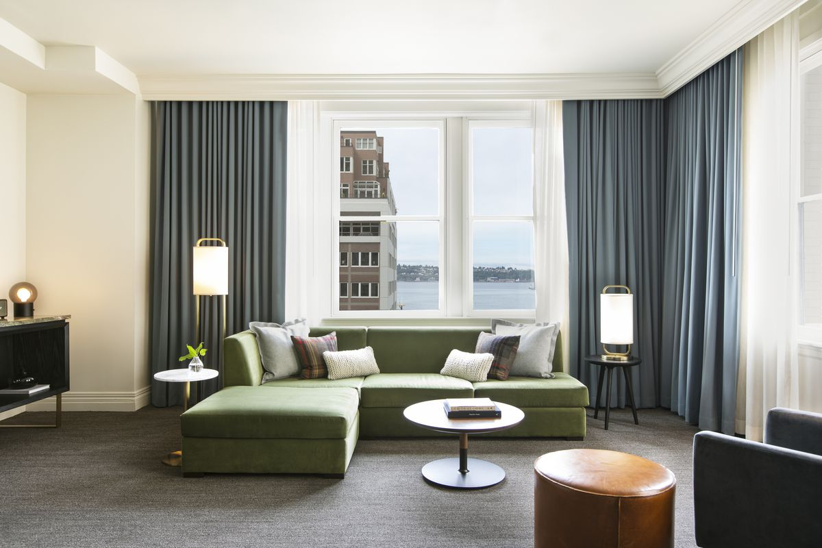 A white living room with slate, hotel-style curtains and a view of a brick building and water through the window. There's a green sectional in the foreground.