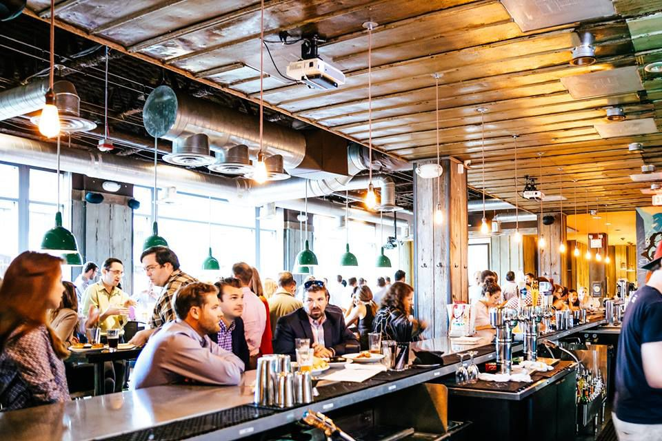 A crowd of people gathered at a bar with exposed wooden beams above