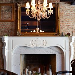 A marble-fronted fireplace, glass chandelier, antique framed mirror ...