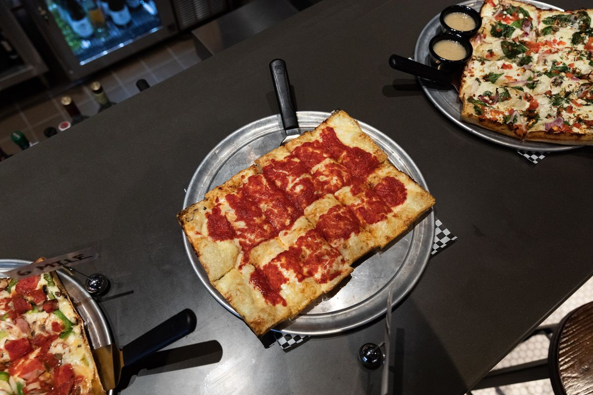 A square cheese pizza with red sauce on top sits on a metal tray at the bar.