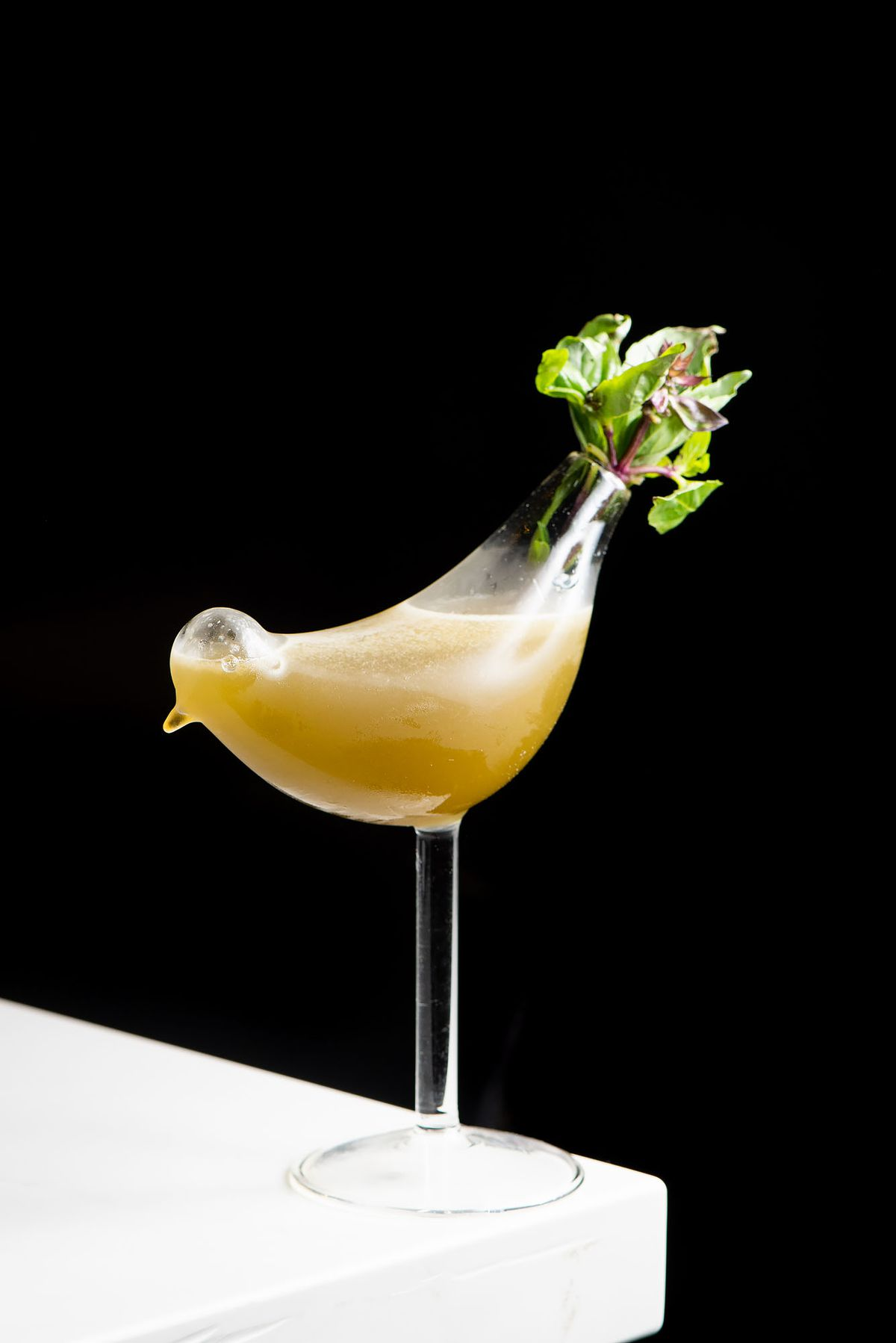 Gran Canaria cocktail at Canary in a bird-shaped glass and mint garnish.