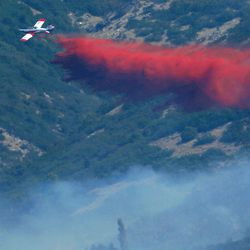 A small plane pulls up as it drops retardant on a fire burning near homes at the mouth of Weber Canyon on Tuesday, Sept. 5, 2017.