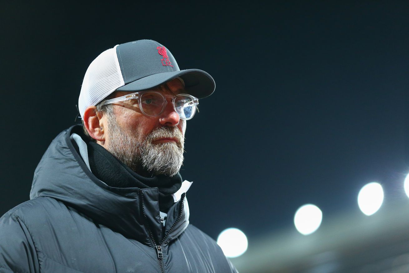 Jürgen Klopp betrays no emotions on the sideline against Everton. He wears an LFC cap and puff jacket.