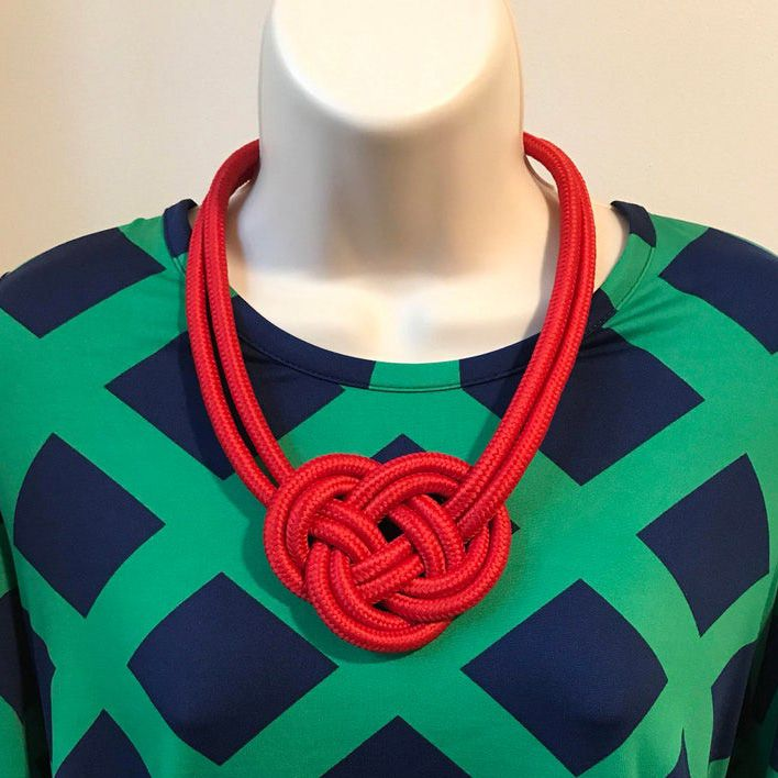 Red knot necklace on a bust wearing a green and blue shirt.