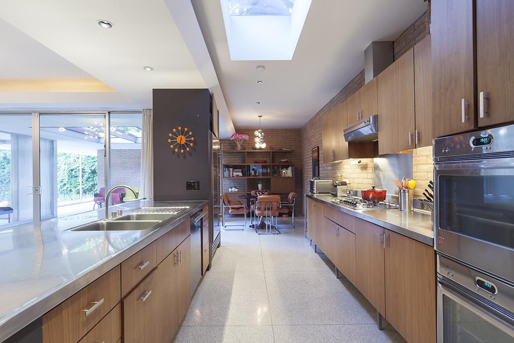 A midcentury modern kitchen with wood cabinetry, metallic countertops, a table and chairs, a skylight, and bookshelves.