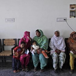 In this Monday, April 2, 2012 photo, Pakistani women wait their turn to claim money at the Benazir Income Support Scheme Center, in Kallar Kahar, Pakistan. A roomful of Pakistan's poorest women  wait in silence for something many have never experienced: a little bit of help from the government.  It comes in the form of a debit card that is topped up with the equivalent of 30 dollars every three months.