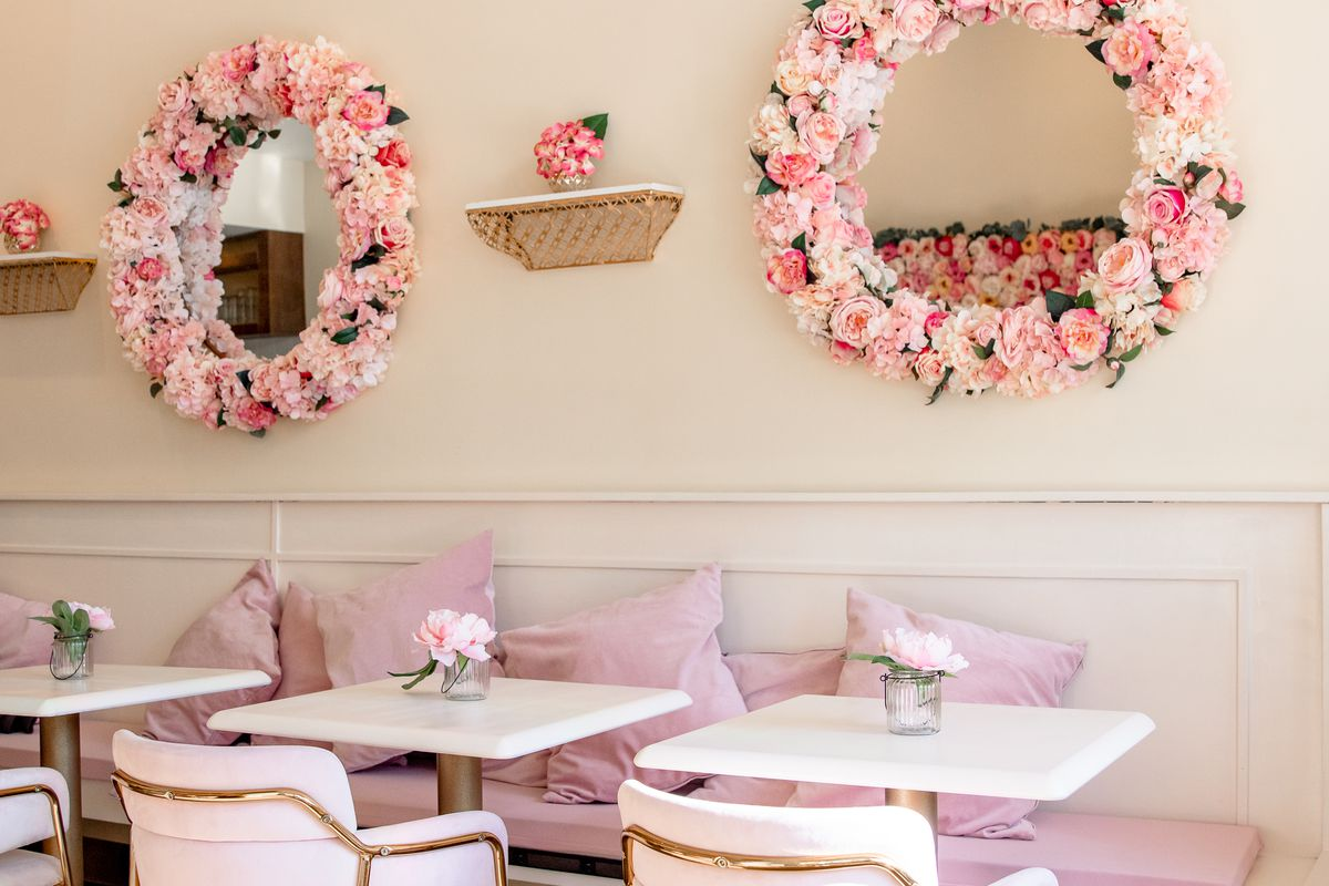 The creamy walls are offset by pale pink pillows on a pink velvet bench, and white tables are flanked by pale pink velvet and gold chairs