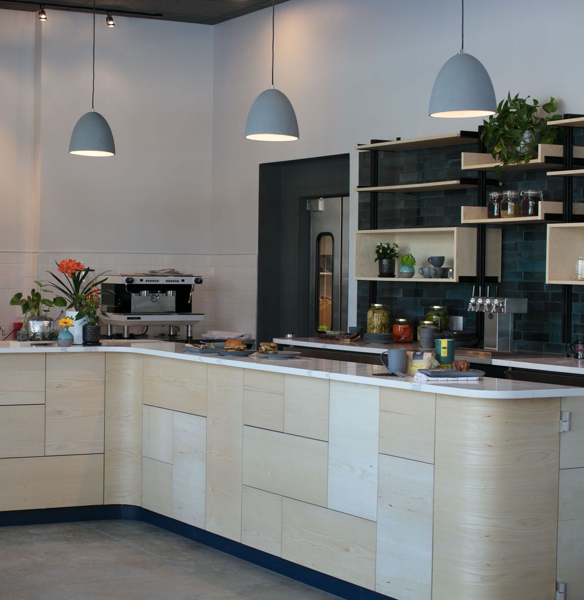the interior coffee bar at the landing kitchen with three hanging pendant lights and a mismatched wood bar