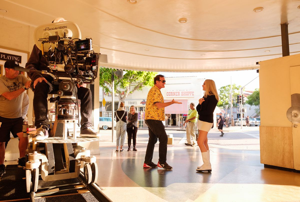 a 35mm camera sits alongside Quentin Tarantino and Margot Robbie on a movie theater set
